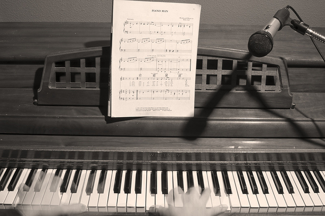 Piano keyboard with phantom hands and Piano man Sheet Music and Mic. Black and white sepia image www.JamesInsogna.com